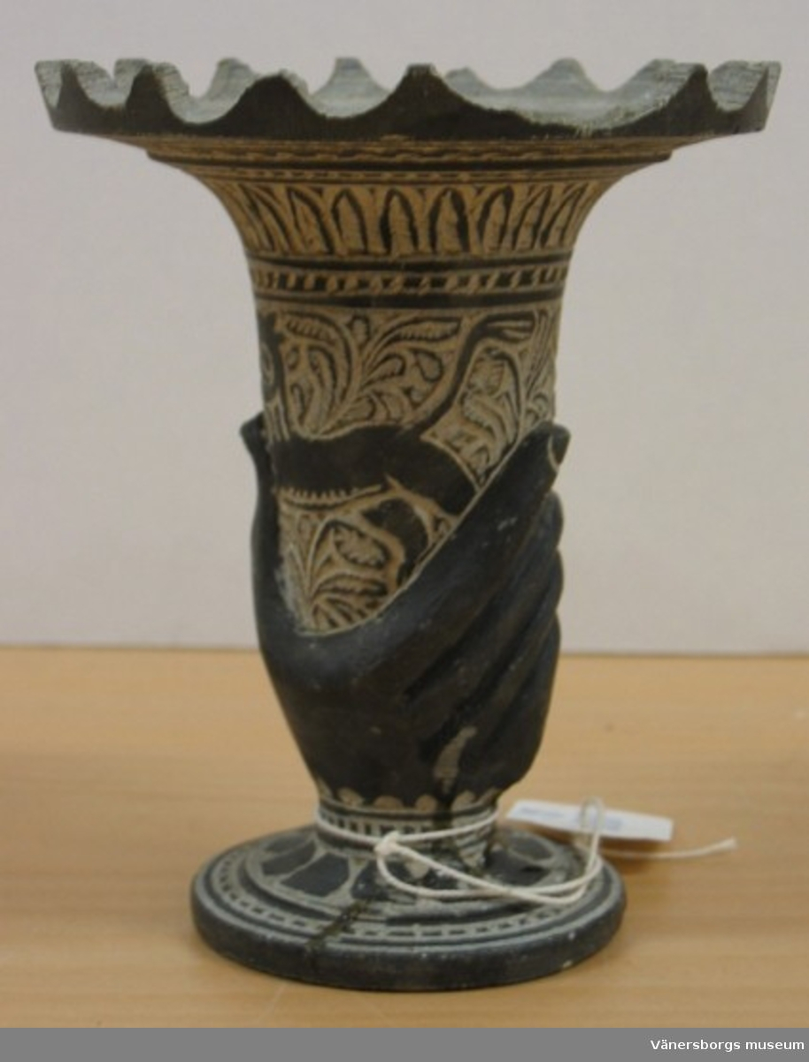 Urna av sten med fotställning och ornament däribland en stor hand, uppstående taggar i kanten, från Mekka.   Avd. Österländska föremål i Ahléns tryckta katalog.