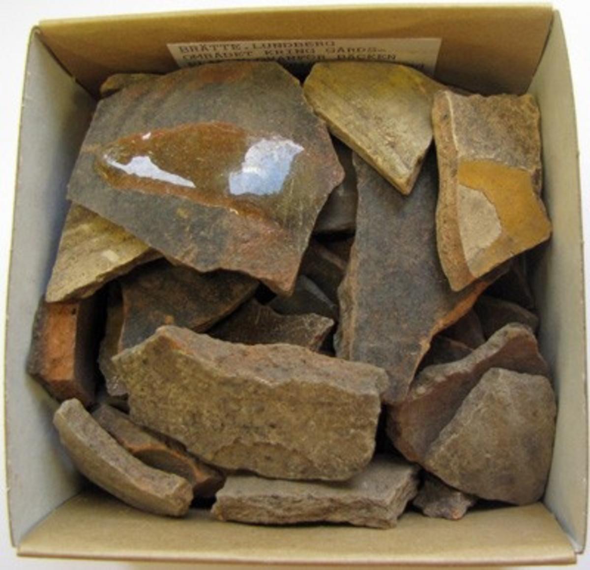 BRÄTTE. LUNDBERG.OMRÅDET KRING GÅRDSPLANEN OVANFÖR BÄCKEN. Rödgods, BII, 50 skärvor.  Danmark, Tyskland och Holland är troliga provinienser för keramiken.  År 1943 utförde arkeolog Erik B. Lundberg från riksantikvarieämbetet en arkeologisk utgrävning av den forna staden Brätte.