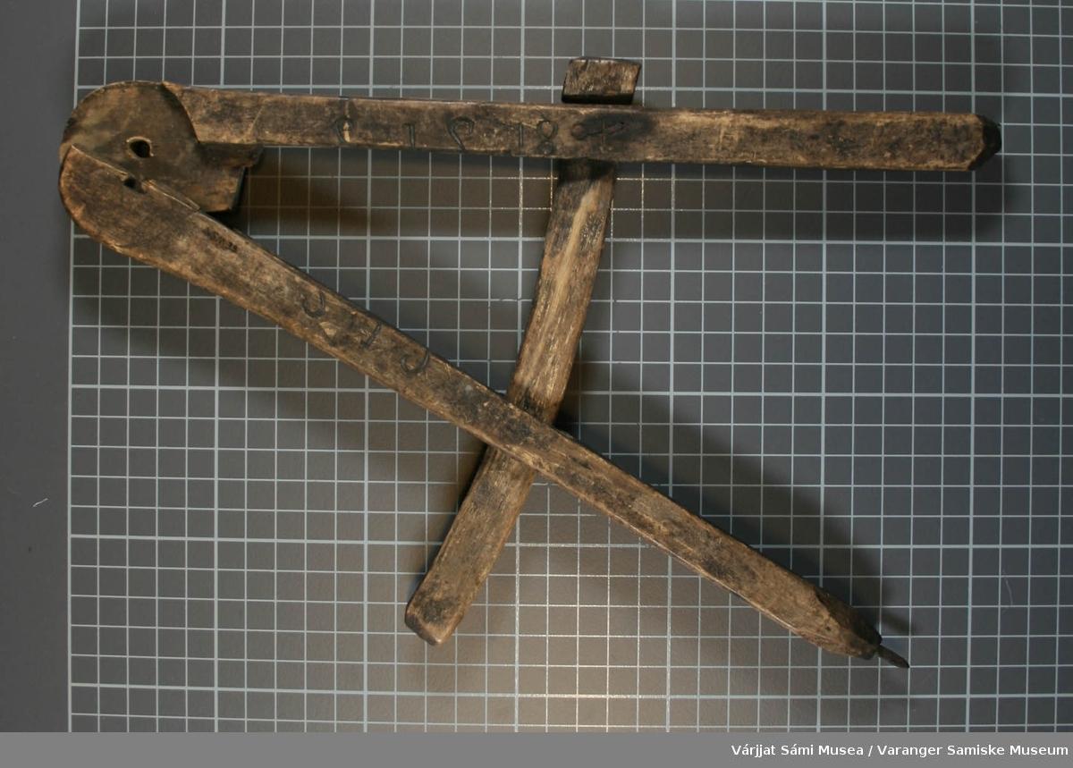 Passer av tre med en spiker av metall som passerspiss. En del av passerhodet mangler. Passeren kan lage sirkler med en diameter på opptil 30 cm.
