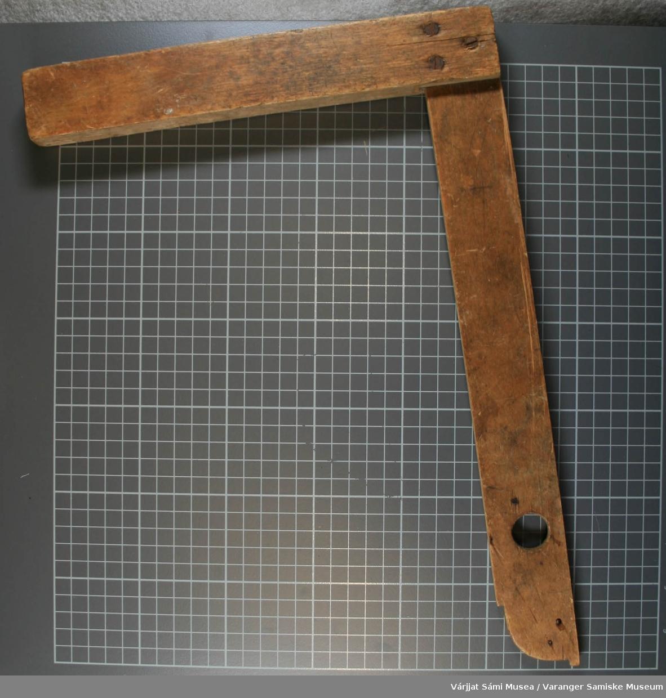 Vinkelen er av tre og består av to deler som er skrudd sammen med tre skruer. Den lengste delen har et hull som har en diameter på 2 cm. Den lengste delen har avrundet ende.
