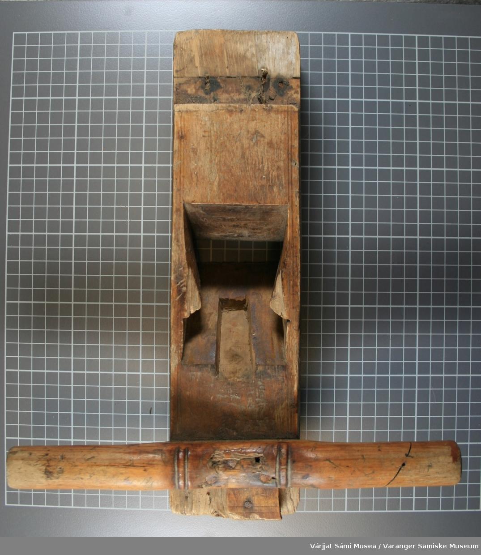 Tomannshøvel av tre. Ett håndtak er spikret fast, det andre håndtaket mangler. Tapp og stål mangler.