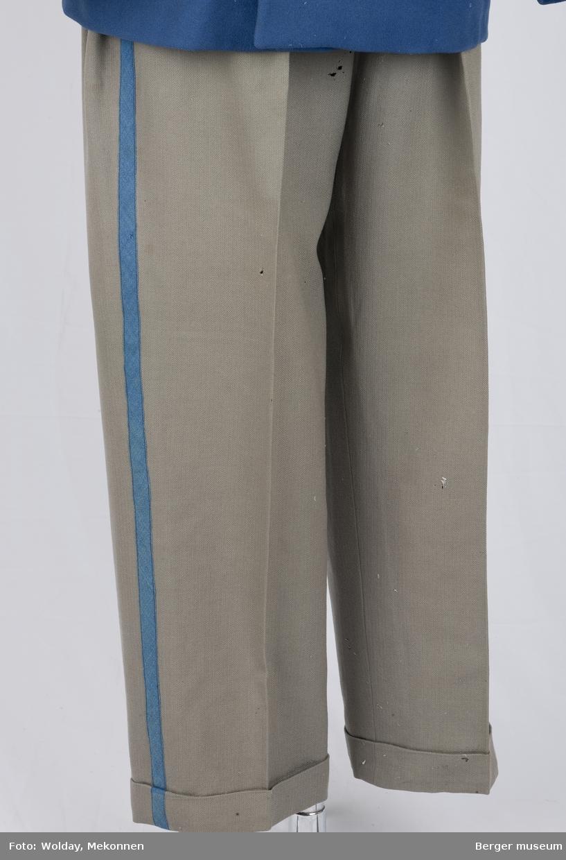 Buksene er grå med en kornblå stripe nedover fra linningen fra begge sider. Buksene har sidelommer, baklomme og en liten lomme foran. Linningen er foret.