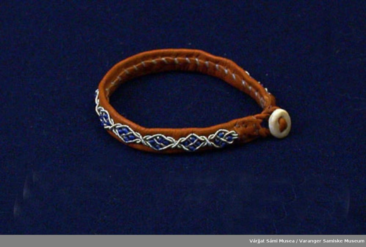 Et armbånd av reinskinn, tinntråd og perler. Lukkes med en knapp av horn.
