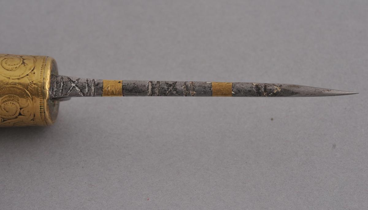 Kniv med smidd blad. Innfelt messing i overkant av knivblad. Dekor med mønster av strekar og kryss ved sida av messingfelta. Lite igjen av knivbladet, slipt ned. Skaft av tre. Holkar av messing som er sisselera/ gravera.