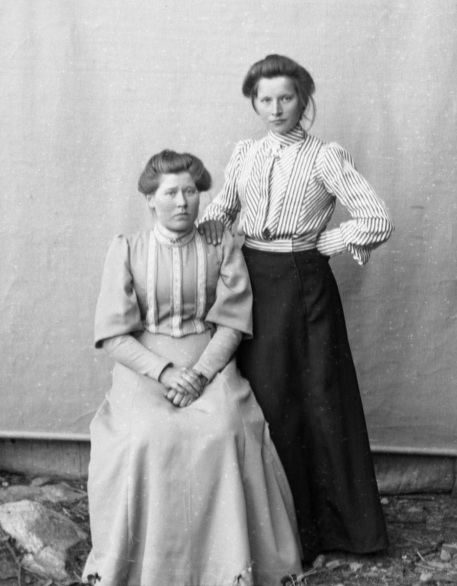 Kvinne kledd i stripete bluse og mørkt skjørt, stående sammen med kvinne som sitter, kledd i lys kjole. Lerretbakgrunn