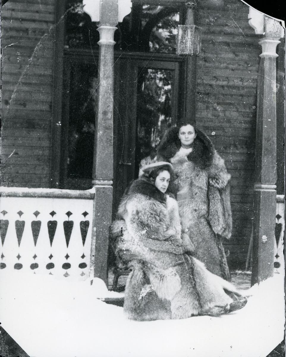 To kvinner kledd i store pelskåper, i inngangsparti til sveitserstilsbygning