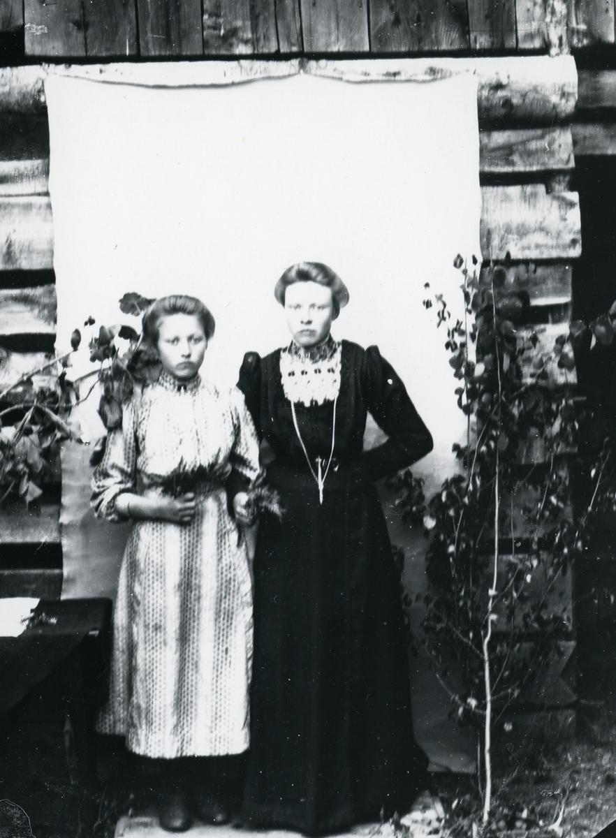 To kvinner arm i arm, med blomster, fotografert med bjørkekvister foran lerret, i helfigur