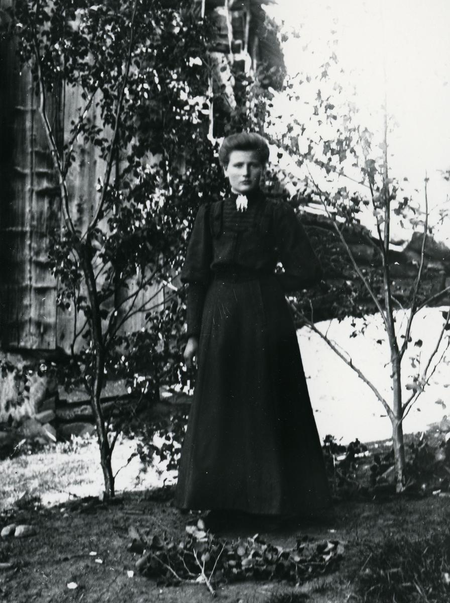Ung kvinne i helfigur, kledd i mørk kjole med sølje, avbildet foran låve og låvebru