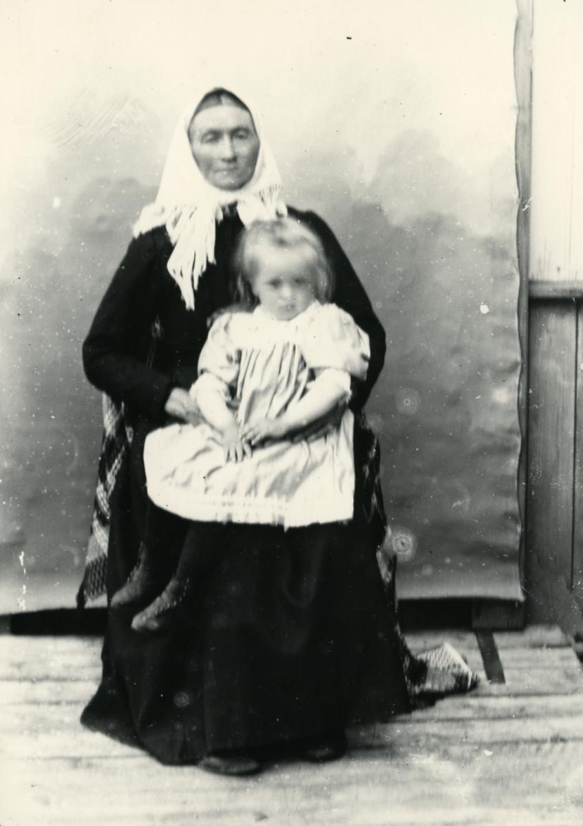 Eldre kvinne med skaut, sittende foran lerret, med liten jente på fanget