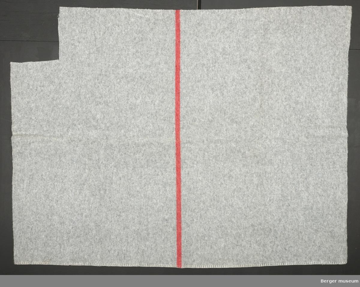 Ensfarget grått medf en rød stripe i midten i lengden. Teppet har vært helt, men så er det klippet av det og blitt brukt til prøver.