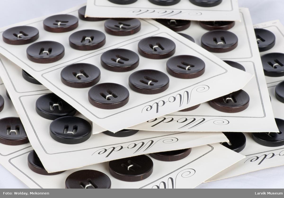 Eske med lokk innholder 6 brett à 12 knapper. Runde store  knapper med 2 ovale hull til feste