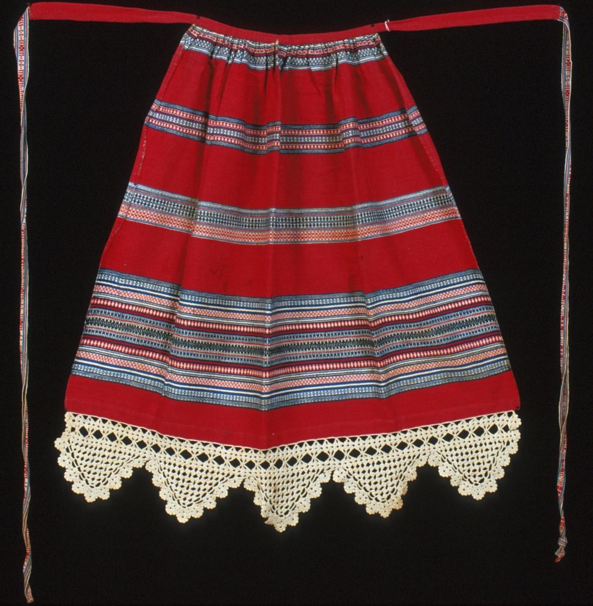 Förkläde vävt i inslagsrips med breda rosengångsbårder på tvären. Nedtill är förklädet kantat med en grov, virkad uddspets i oblekt bomullsgarn. Röd botten i inslagsrips med fyra rosengångsbårder i tre nyanser blått samt vitt och rött. Tre bårder är 45-55 mm breda, den fjärde, nedersta bården är 170 mm bred. Förklädet är rynkat mot linningen, bredden upptill är 270 mm. Linningen, i samma röd tyg som bottenväven, är förlängd i var sida och utgör början av knytbanden, i sin helhet är den 810 mm lång. Påsydda mönstervävda knytband i var sida; ca 930 mm långa. Stadkanter i sidorna, 20 mm bred fåll nedtill. Den virkade spetsen är 140 mm som bredast. Handsydda sömmar. Varp i vitt bomullsgarn, 12 trådar/cm. Inslag i kulört 1-trådigt bomullsgarn, ca 40 inslag/cm. Bandet: Varp i vitt, rött och två nyanser blått bomullsgarn.Inslag i vitt bomullsgarn. Plockat mönster