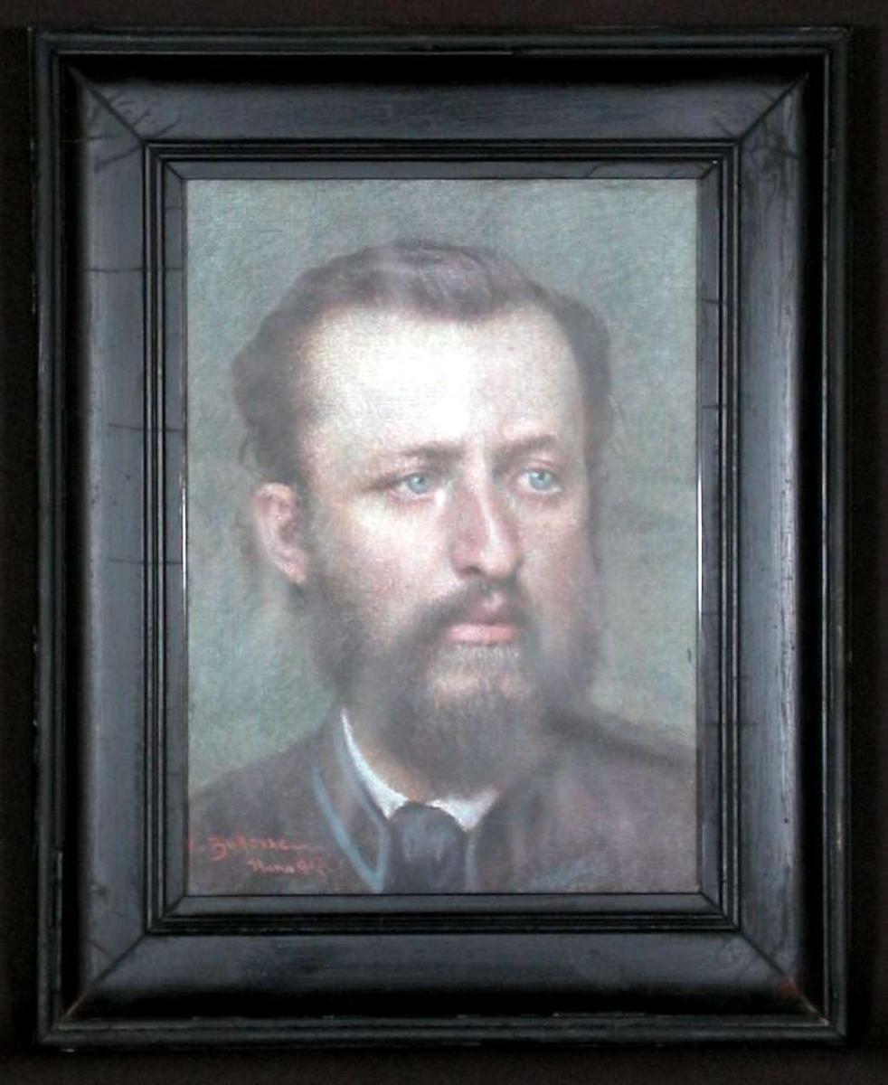 Portrett av en mann i 30-50-årene, fullskjegg, slips.