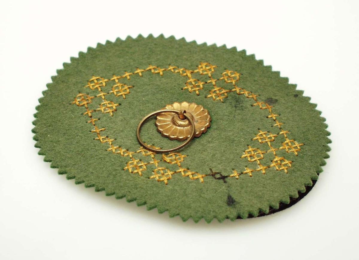 Grønn pennetørker i filt med oval form. Ytterkant på øverste lag er taggete. Gult korsstingsbroderi med moulinegarn på grønn filt. Under to lag svart filt, ovale 7x9cm. Messingnagle med rosett og ring på forsiden holder de tre lagene sammen.
