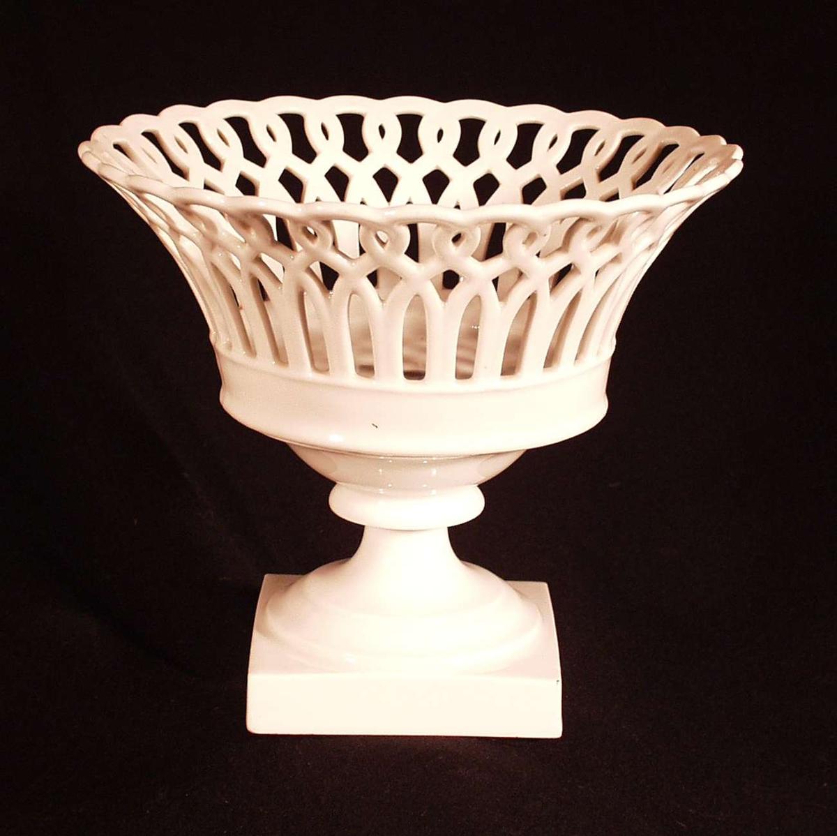 Rund, utoverbøyd m. gjennombrutt flettverk og  tvunget overkant på rund profilert stett .Vasen festet til fotstykket m. skruanretning. Firkantet fotstykke. Andre mål: fotstykket: 10x10.