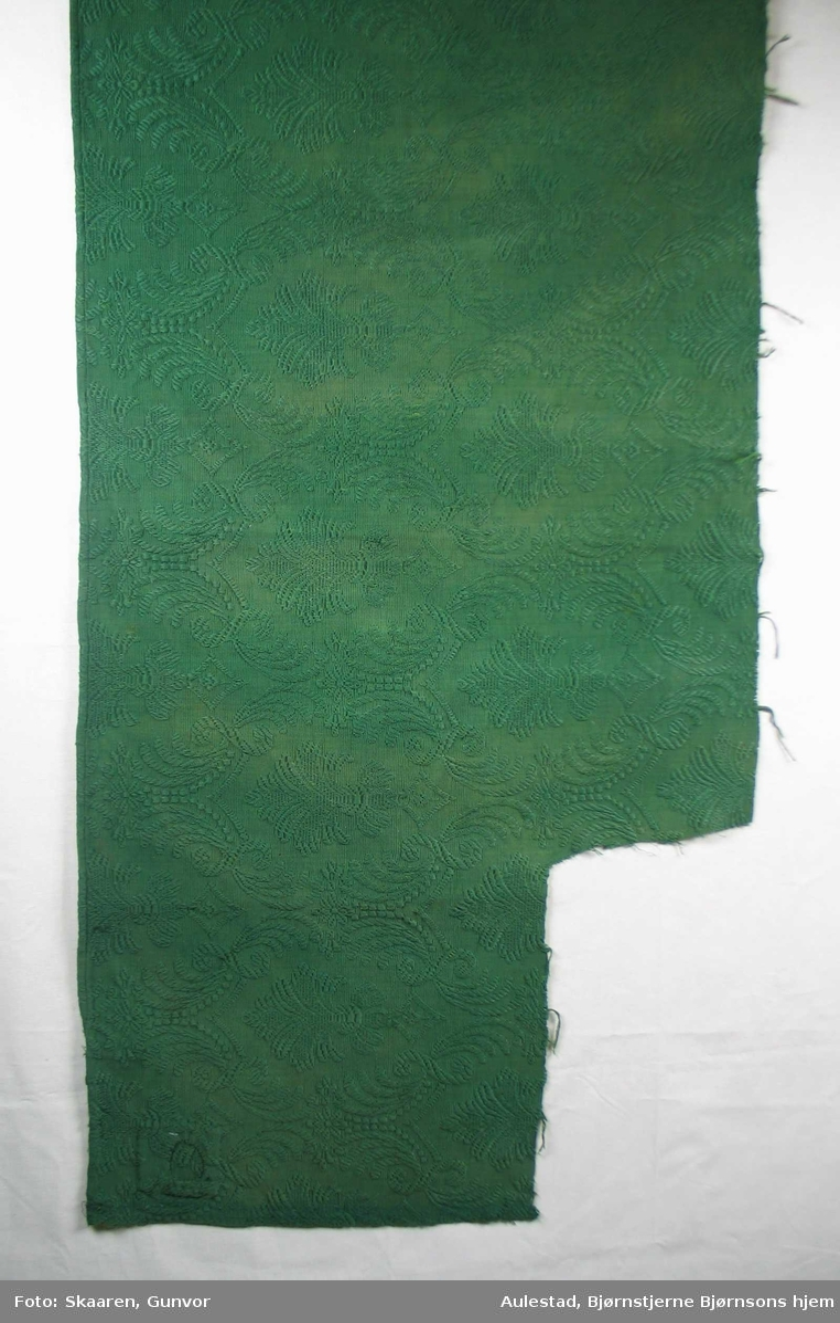 Mørk grønt jacquardvevd portierestoff . Mønstring ved flottering av mercerisert bomull på ripsbunn. Motiv: Palmett i oval form, omgitt av bladverk; stilisert. Mønsterets rapport er høyden 37 cm, i bredden 20 cm.
