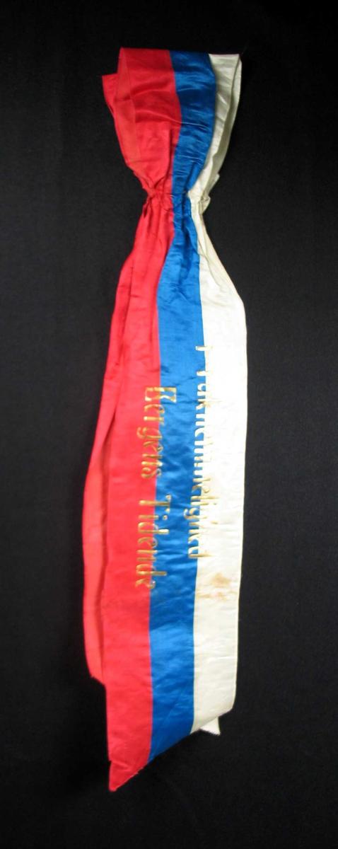 Begravelsessløyfe i hvit, rød og blå silke med tekst i gull.