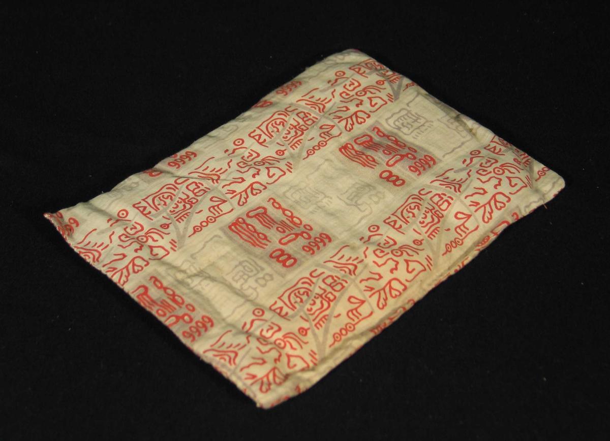 Vattert madrass til dokkeseng i mønstret rødt bomullsstoff.