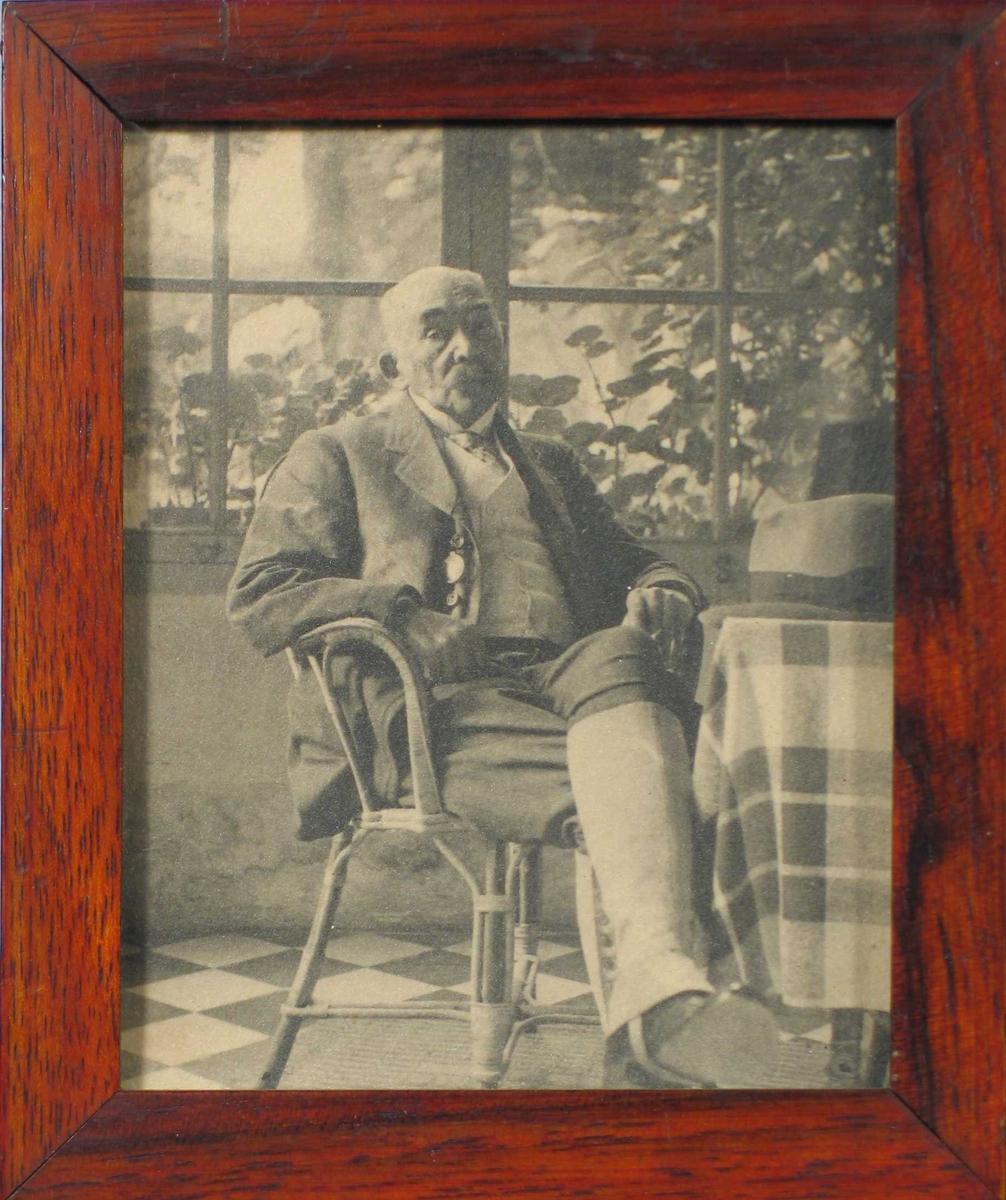Eldre mann sittende ved et bord foran vindu. Han er iført jakke, dobbeltspent vest og lange gamasjer. Hatten ligger på bordet.