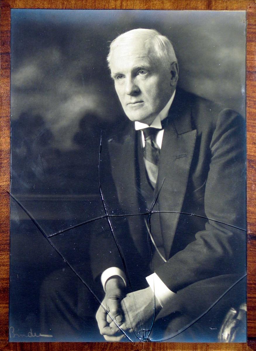 Portrettfotografi av middelaldrende mann sittende på stol, lent fremover med armene hvilende på lårene og hendene om hverandre. Han er fint kledd i mørk jakke med stort revers og bredt stripet slips, vest med urkjede og stivet hvit skjorte.