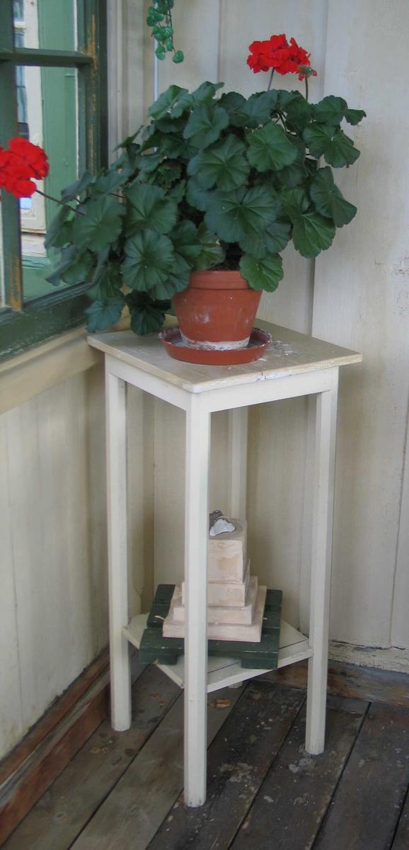 Pidestall i tre med fire bein, firkantet plate og hylle. Den er malt lys gul.