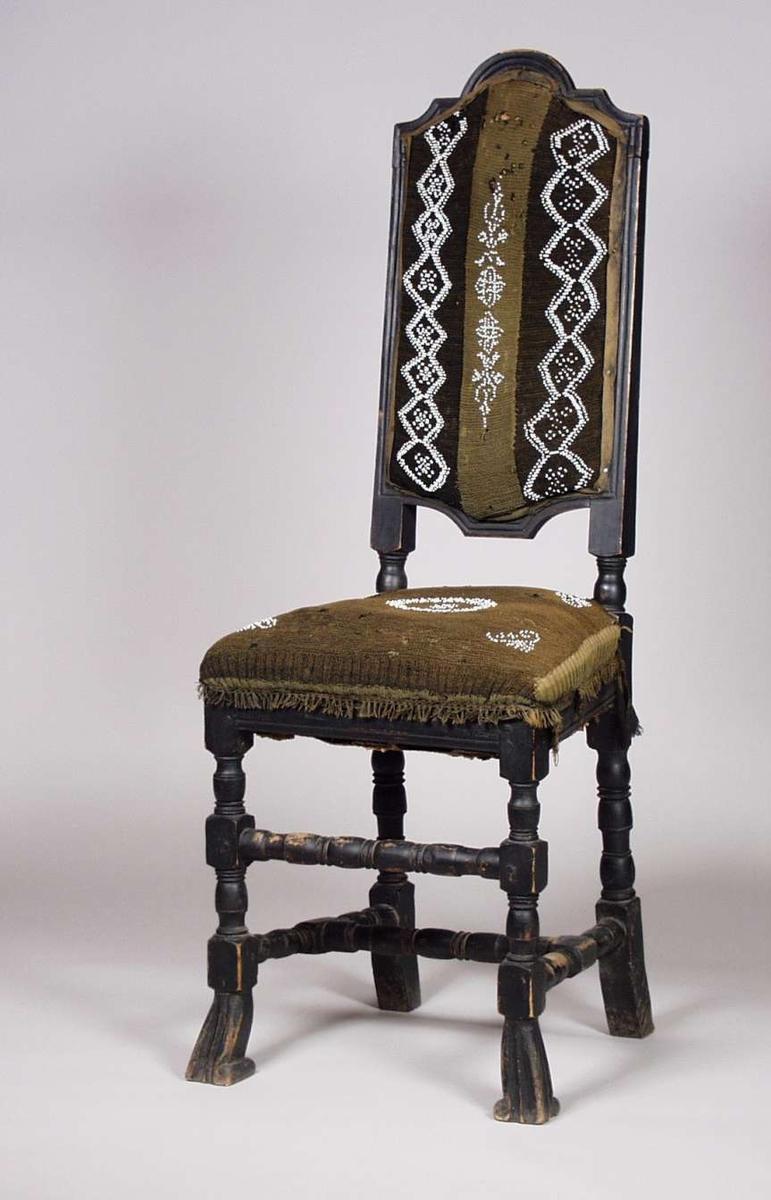 Svartmalt stol med dreide ben. Grønn strikket rygg og setetrekk dekorert med hvite glassperler.