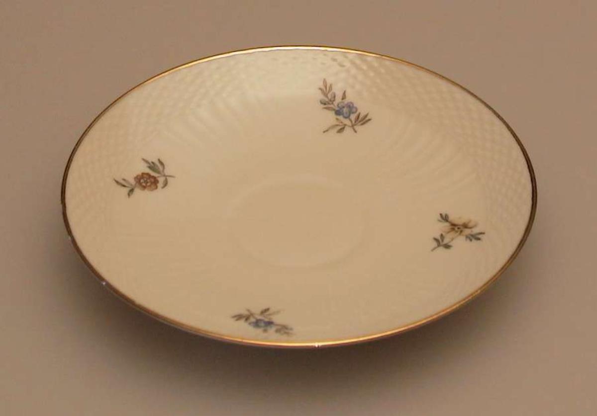 Skåla har flerfarget blomstermotiv på lys beige bunn. Gullkant. Riflet mønster i godset.
