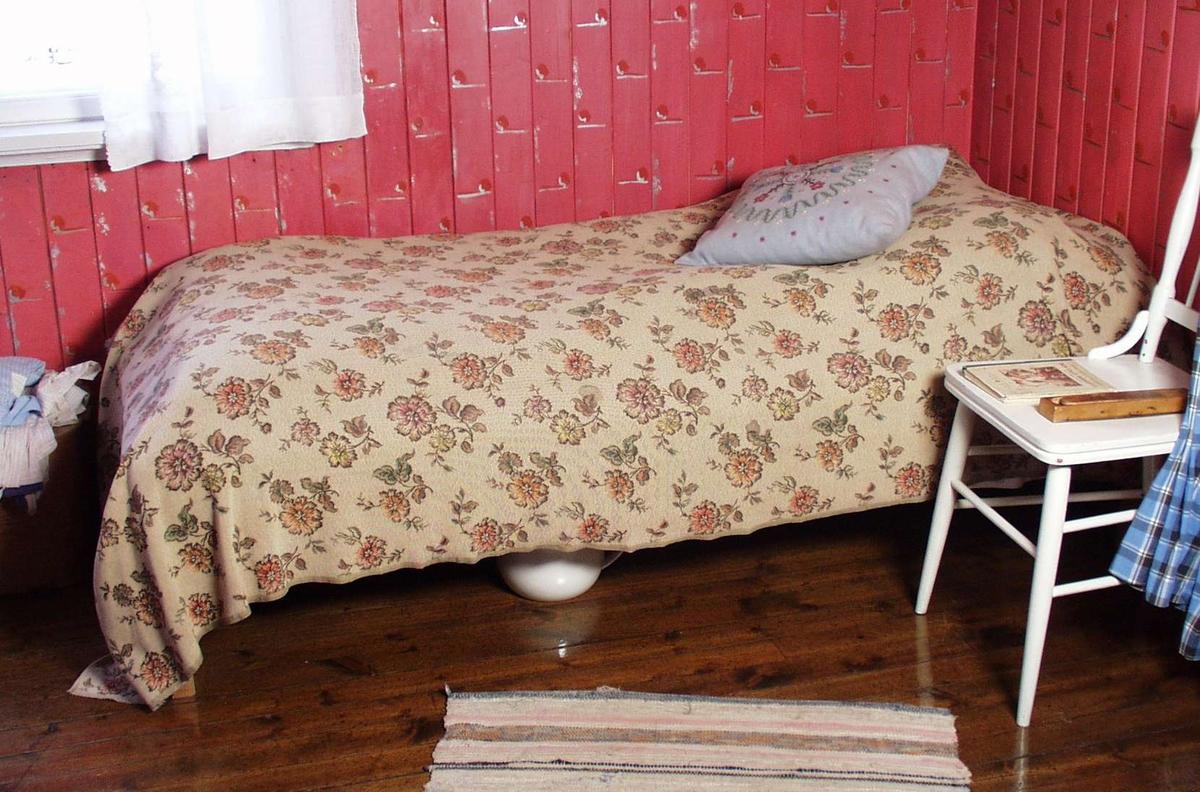 Divan med fjærmadrass der den øverste delen er fylt med halm. Madrassen er stiftet til sengen og er laget av blått blomstret kraftig stoff. Rammen og beina er laget i ubehandlet treverk.
