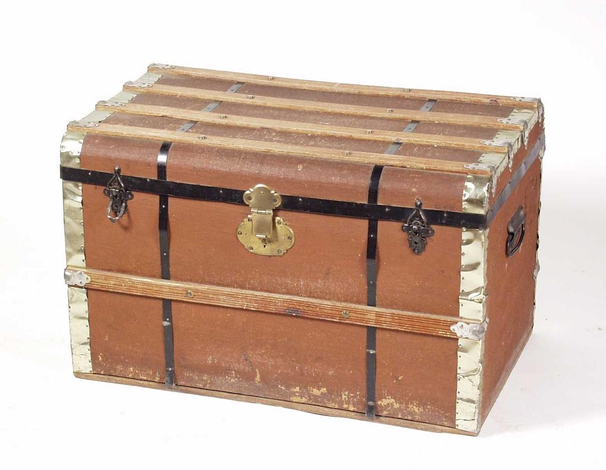 Koffert av tre trukket med brunmalt strielerret. Hjørnene er forsterket med blankt jernblikk, mens kofferten er forsterket med svarte jernbånd rundt kofferten på tvers. Lokket er avrundet på langsidene, og er forsterket med fire trespiler med riller. Forsiden har en trespile og baksiden har to trespiler. Bærehåndtak på sidene og to svarte jern låseklemmer og et messingfarget koffertlås på framsiden. Innvendig er kofferten trukket med blåstripet papir.Plass fir løs skuff, men den mangler.