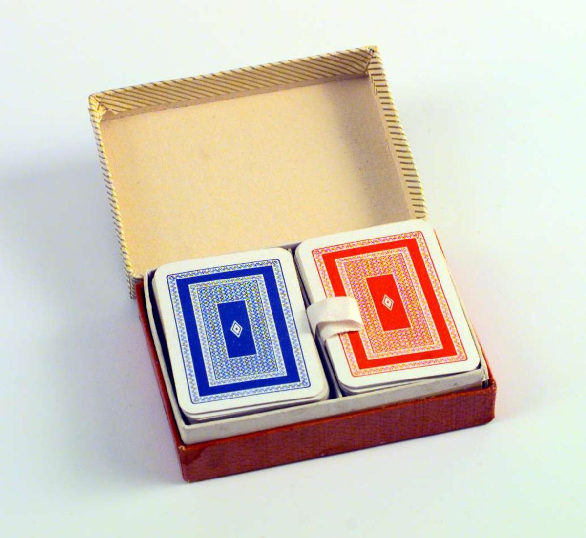 To kortstokker i en eske. Den ene kortstokken er rød og hvit, den andre blå og hvit. Esken er rosa med stripete gult og gyldent lokk.