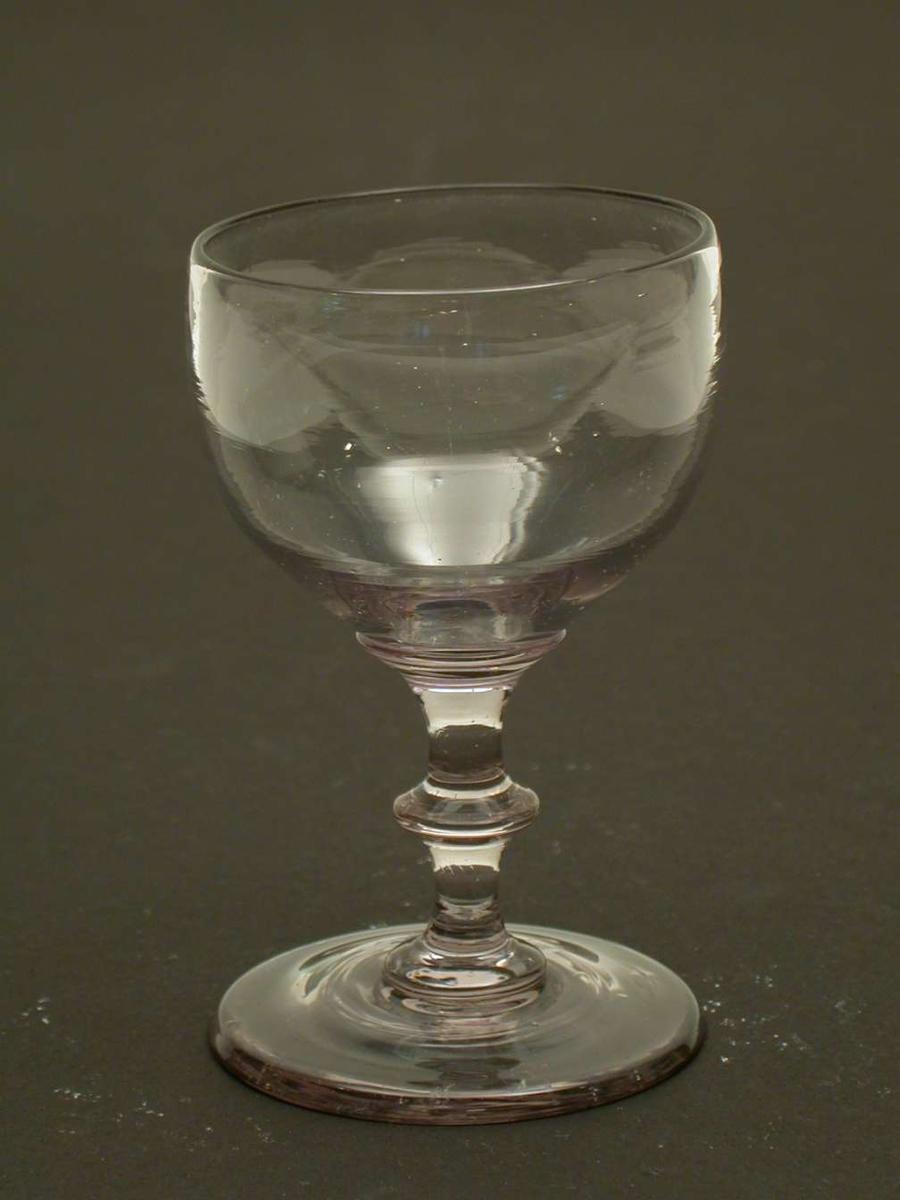 Vinglass, dessert, med skive i stetten. Glasset er svakt sotfarvet med et lilla skjær.