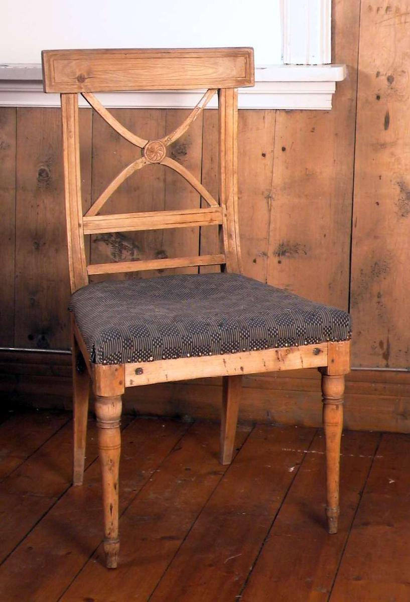 Trehvit spisestuestol med Andreaskors i ryggen og med stoppet sete. Stoffet i setet er blått og beige i et rutemønster. Trekket er slitt. Stolen er reparert i korset i ryggen.