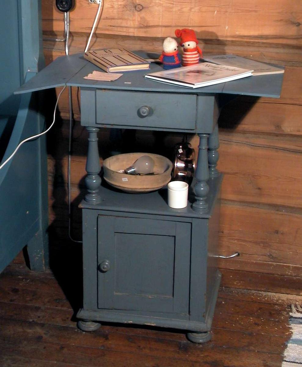 Bondeblått nattbord i to høyder med åpent rom mellom. Øverst er det en skuff, nederst et skap. Nattbordet har klaffer. Det står på fire runde, dreide føtter.