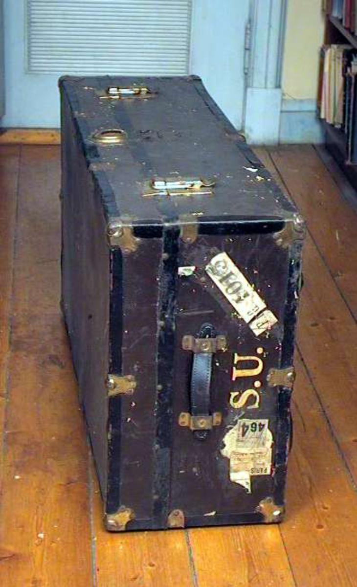 Koffert av finér med sorte metallbeslag (blikk). Kofferten er brunmalt. Den har lærhåndtak på begge sider. Den har lås og beslag av messing. Hovedlåsen er i stykker, men den ligger i kofferten.
