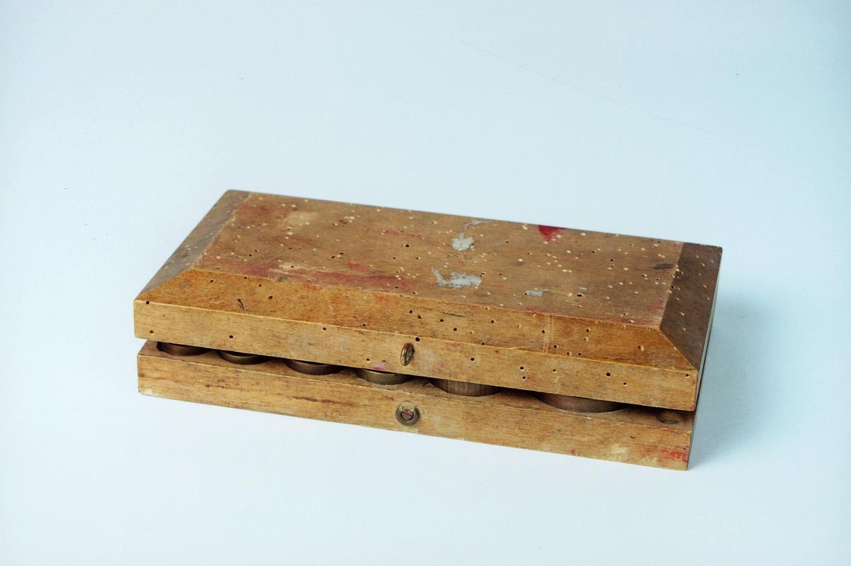 Loddkasse av bjørk og inneholder 10 lodder i messing (3 lodder mangler, 5, 2 og 1 g) på 500, 250, 125, 100, 40, 2x20, 2x10, 2 g