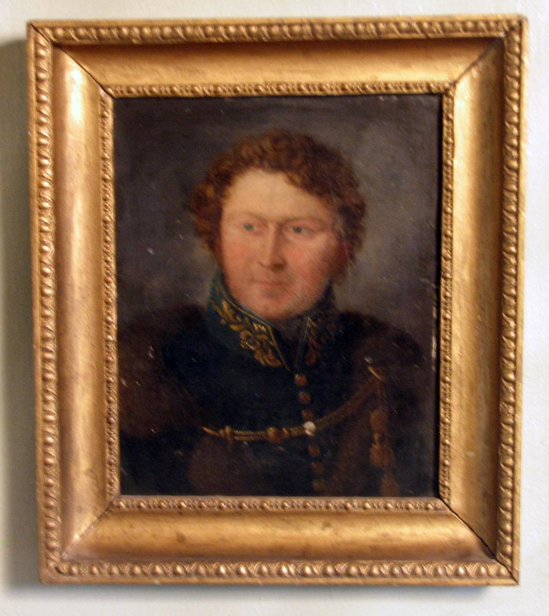 Rektangulært ; ramme: plastisk dek. Brystbilde; mann i uniform; ansikt noe venstrev.,rødl. karnasjon,; brunt, krøllet hår; skinnkant. kappe over skuldrene; gråblå bakgr.