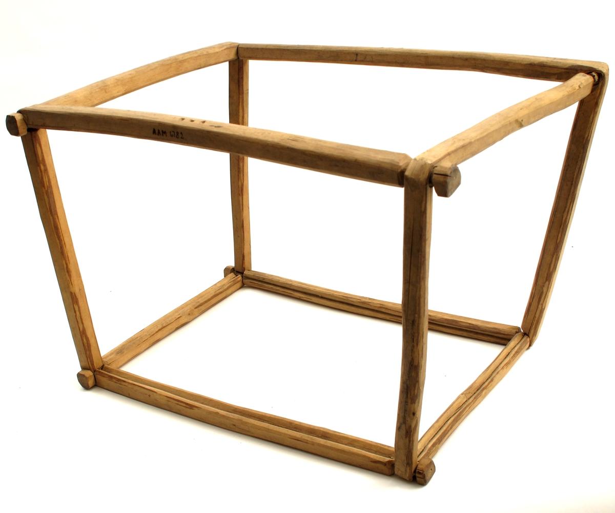 Kurvramme laget av fire trestykker, alle med tilnærmet kvadratisk tverrsnitt, hvert trestykke bøyd to ganger i 90 graders vinkel. Bøyene kniper om endene på tilstøtende trestykke, slik at det dannes en firkantet ramme, første steg i produksjon av en kurv. Det er skåret spor for innsetting av kurvens vegger.
