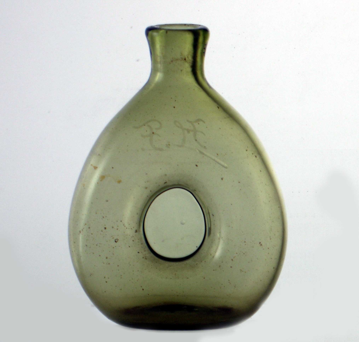 Karaffel av grønt glass.   Litt bred lerkeform med dråpeformet lukning  pm. Bokstavene i flussgravyr på halsen.  Flasken er blåst,