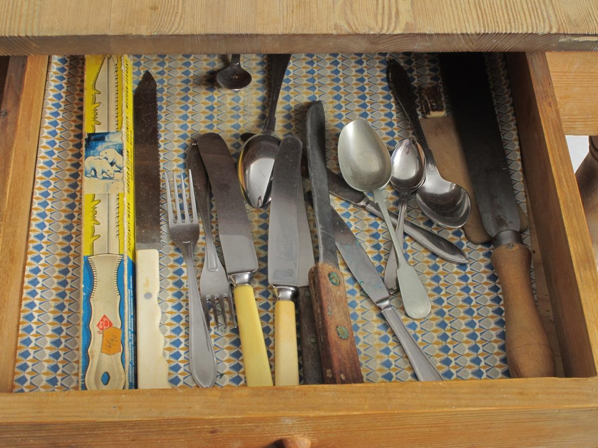 Kjøkkenbord, klaffer i begge ender, holdes utslått av uttrekkbare spiler. Bordplata er limt sammen av smale bord.  Bordskuff, inneholder bl.a kniver. Presis bearbeiding av alle deler.