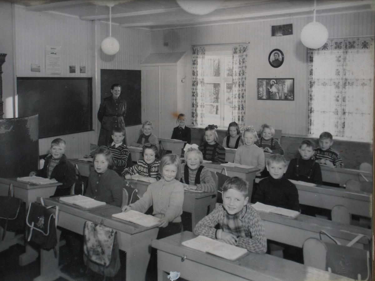 Skoleklasse fotografert i klasserom, elever ved pulter, lærerinne i bakgrunnen.