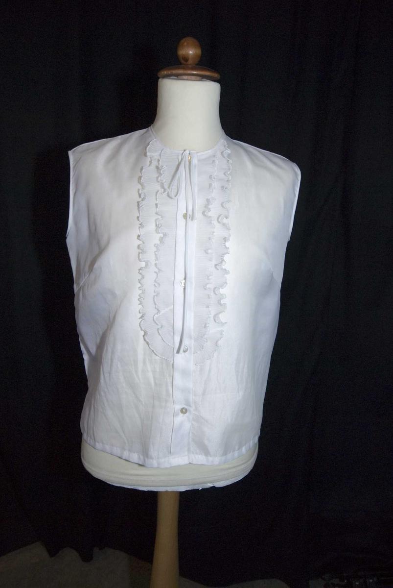 Hvit damebluse uten ermer, med lukking foran og pliserte rysjer langs kneppingen. Knytesløyfe i halsen.