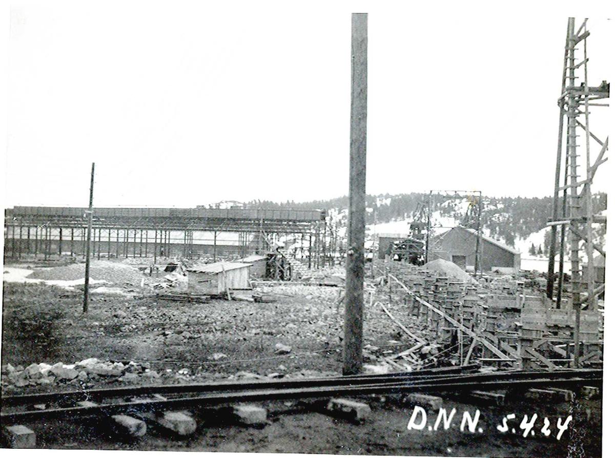 """""""05/04-1924"""" Nitriden. Bygging av stekeribygning for steking av elektrodekull. Jernkonstruksjon. Taubanemast til høyre. Lagerhus for bauxitt. Kran på kai. Skinnegang for internt transport i forgrunnen. Tromøy i bakgrunnen."""