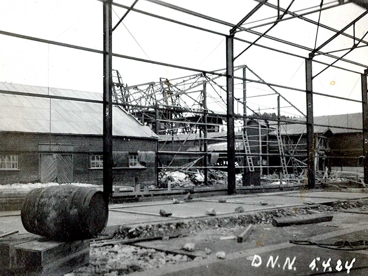 """""""05/04-1924"""" Nitriden. Stekeribygning for steking av elektrodekull under bygging. Jernkonstruksjoner. Tjæretønne og lagerbygning til venstre. To kraner på kai sees i bakgrunnen."""