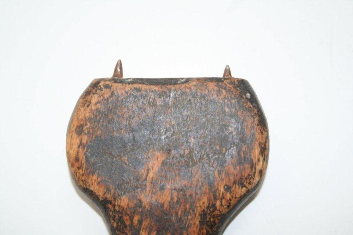Flatt trestykke, buer ut på på hver side i den ene enden, hull i den smale enden. 2 pigger.