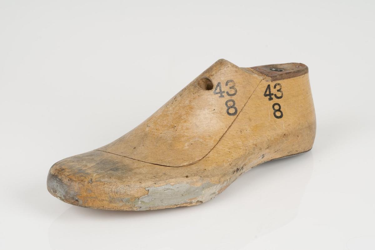 En tremodell i to deler; lest og opplest/overlest (kile). Venstrefot i skostørrelse 43, og 8 cm i vidde. Hælstykket i metall. Lestekam i skinn.