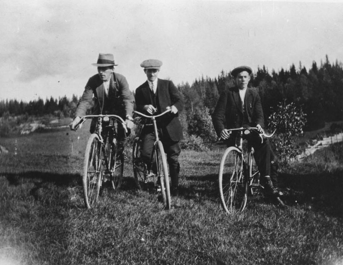 Gruppebilde. Tre menn på sykler.