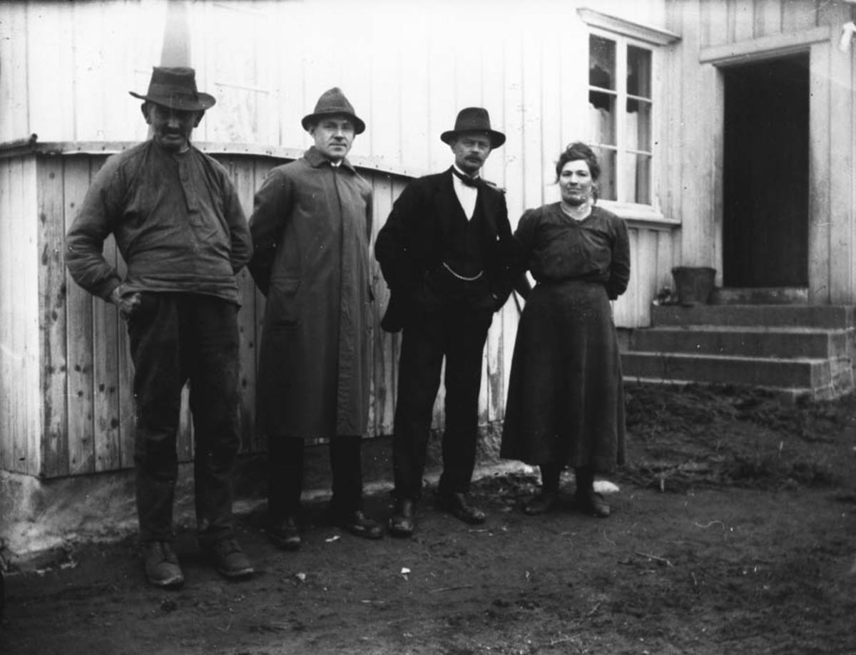 Tre menn og en dame utenfor et hus