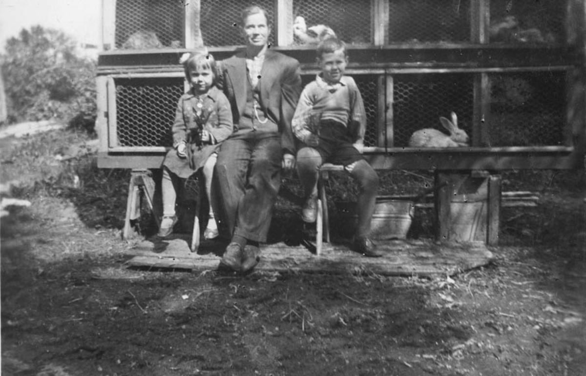 En mann og to barn  foran et kaninbur.