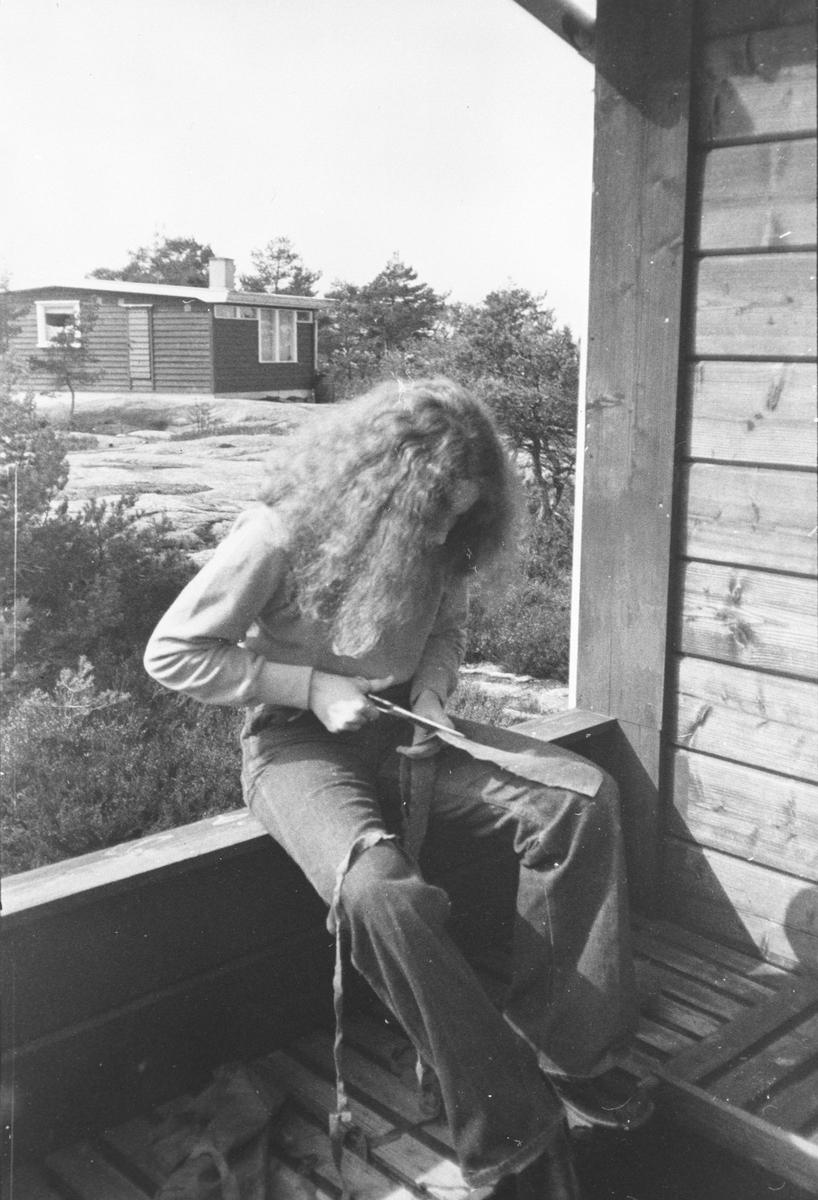 Pike sitter på hytteveranda med filler og saks.
