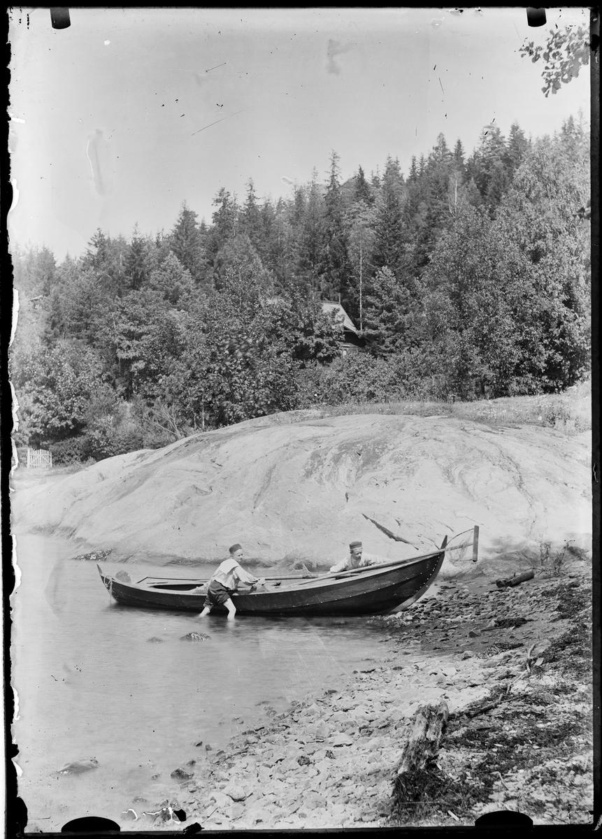 To gutter drar båten på land.
